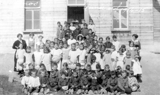 Une groupe d'élèves et enseignantes, dont Mlles Vézina, devant la chapelle-école en 1915. SHA – Fonds Pierre Trudelle