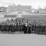 Mgr Desmarais, évêque du diocèse d'Amos avec un groupe d'étudiantes de l'École normale en 1960. Au fond, on aperçoit le Séminaire d'Amos. SHA-Fonds Studio Morasse / H. Dudemaine