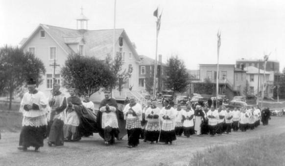 Cérémonie d'intronisation de Mgr Desmarais, premier évêque du diocèse d'Amos, en 1939. À l'arrière-plan: l'ancienne chapelle-école qui sert d'évêché jusqu'en 1946. SHA – Fonds Société d'histoire d'Amos.