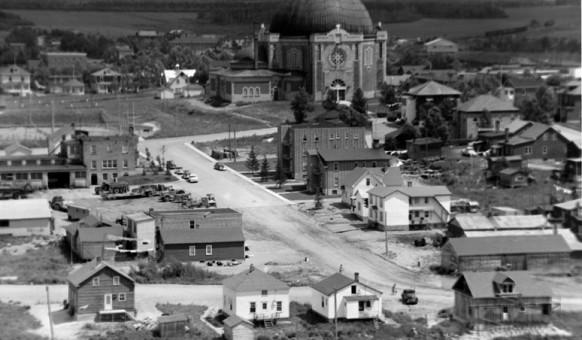 Vue générale du secteur nord-est de la ville, entre 1950 et 1955, près du boulevard Mercier et de la 2e Avenue Ouest. On y voit la cathédrale, le terrain de tennis sur la 3e Avenue, l'édifice de la Société d'entreprises générales et la chapelle-école. SHA – Coll. Ville d'Amos